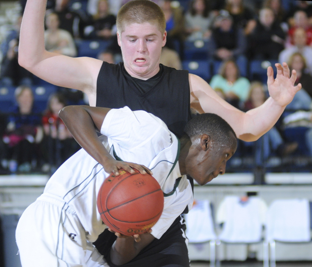 Hall-Dale's Brian Allen tries to defend Serge Nyirikamba of Waynflete during their Western Class C boys' basketball semifinal Thursday night at the Augusta Civic Center. Nyirikamba scored 28 points to lead the Flyers to a 55-35 win.