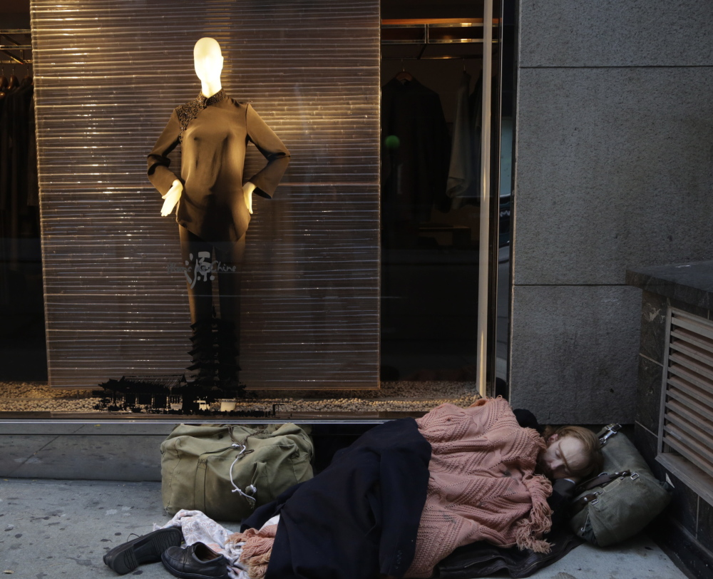 A destitute man sleeps under a holiday window at Blanc de Chine, an elegant clothing store in New York. A Brookings Institution study found that inequality increased across cities even though incomes often fell for wealthy households from 2007 to 2012.