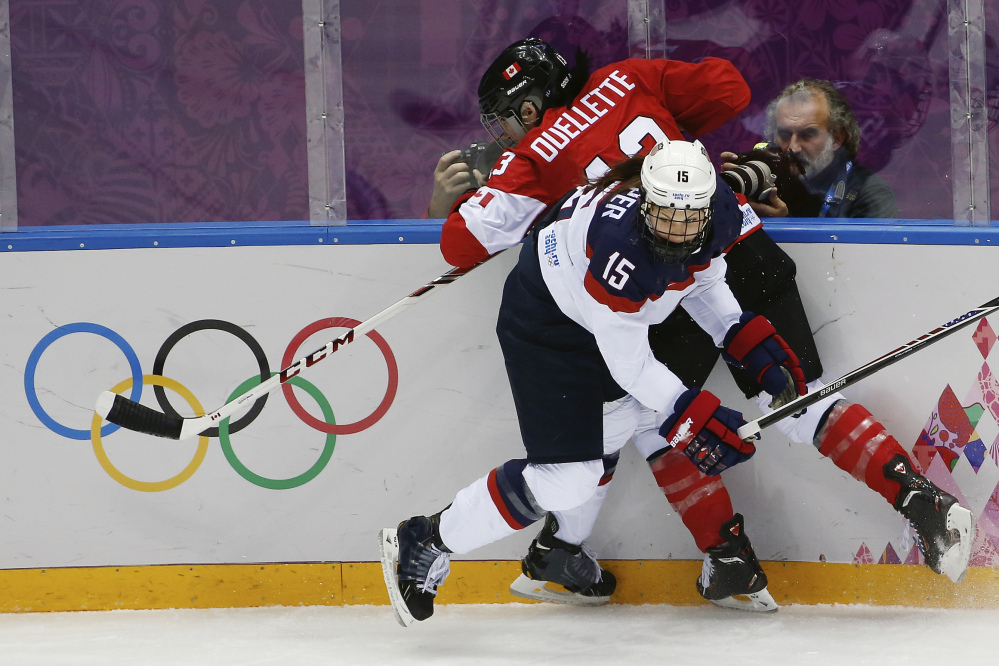Anne Schleper of the United States (15) pins Caroline Ouellette of Canada (13) against the boards during the first period of the women's gold medal ice hockey game at the 2014 Winter Olympics Thursday in Sochi, Russia.