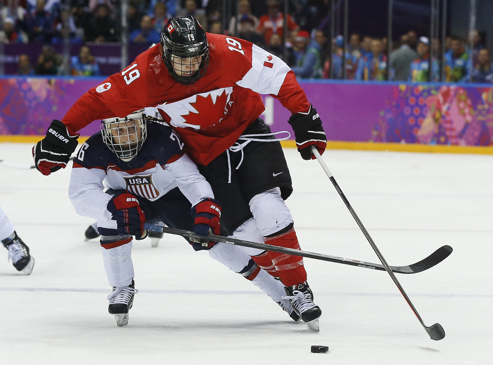 Kendall Coyne of the United States (26) reaches under Brianne Jenner of Canada (19) during the third period of the women's gold medal ice hockey game.
