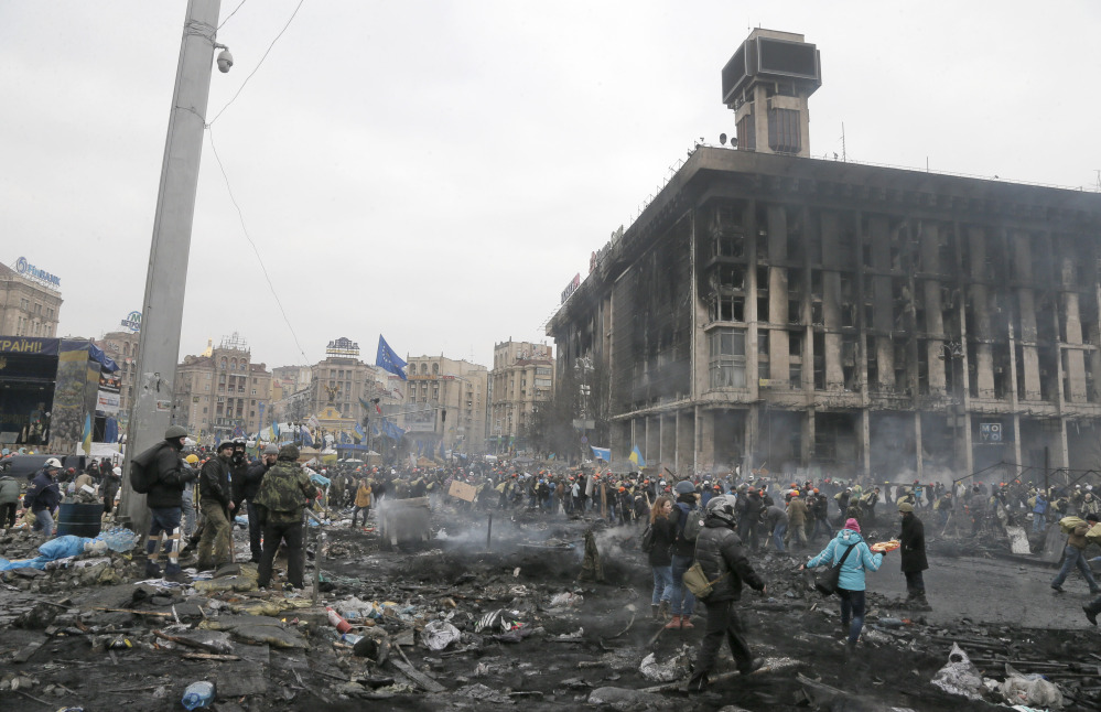 People pass through Independence Square in Kiev, Ukraine, Thursday. Fierce clashes between police and protesters shattered a brief truce in Ukraine's besieged capital Thursday, killing numerous people.