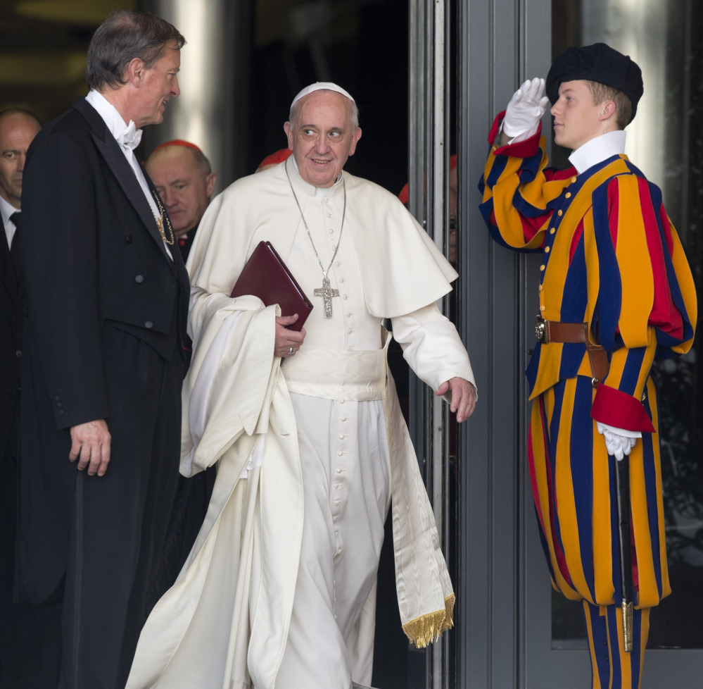 "Pope Francis leaves at the close of the morning session in the Synod hall at the Vatican City on Friday. He urges his cardinals to find ways to provide pastoral care that is 'intelligent, courageous and full of love"" for divorced and remarried Catholics."