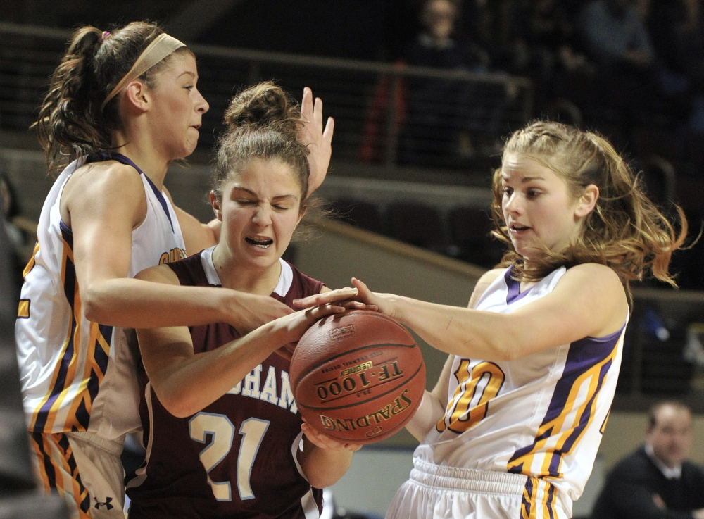 Windham's Luisa Sbardella is fouled while trying to drive between Cheverus defenders Jill Libby, left, and Alisha Starbird during their Western Class A girls' basketball semifinal Friday at the Cumberland County Civic Center. Windham won, 41-36.