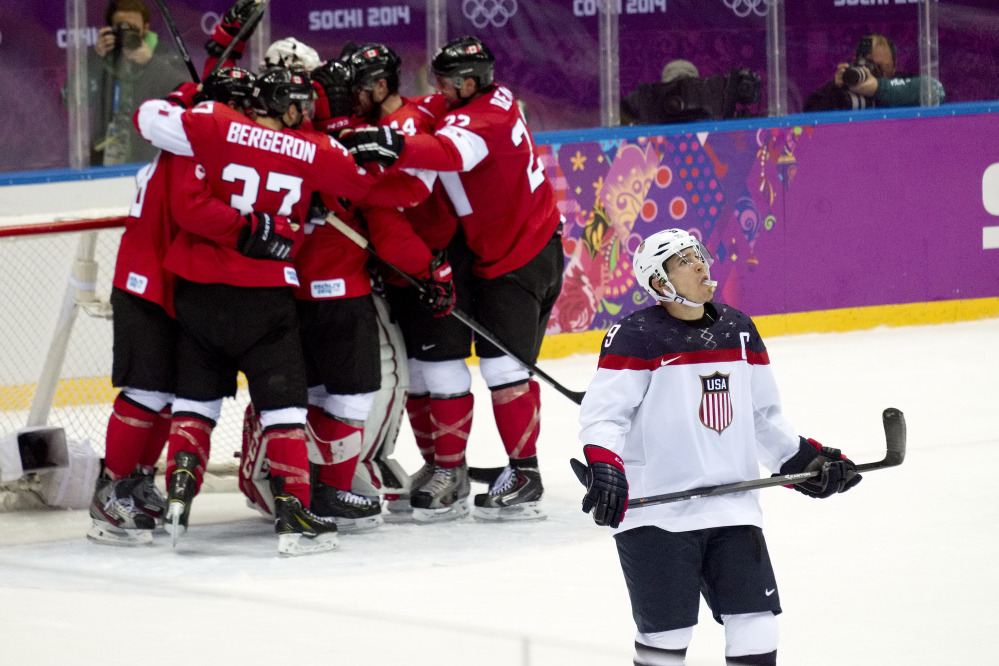 American forward Zach Parise looks up at the scoreboard as Canada celebrates its 1-0 victory in the men's semifinal ice hockey game at the 2014 Winter Olympics on Friday in Sochi, Russia.
