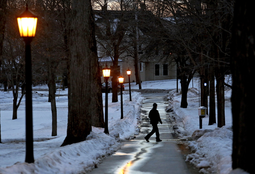 """A man strolls on the Bates College campus in Lewiston at dusk Saturday. A student from the college, John Durkin, was found dead in Rome, where he was studying. In a statement, Bates president Clayton Spencer said: """"This is a time of deep sadness for our community and for so many people who knew and loved John."""""""