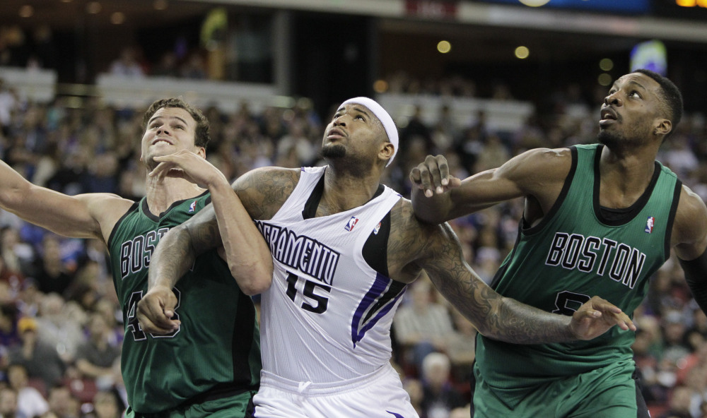 Sacramento Kings center DeMarcus Cousins battles for rebounding position with Boston Celtics' Kris Humphries, left, and Jeff Green in the fourth quarter Saturday in Sacramento, Calif.