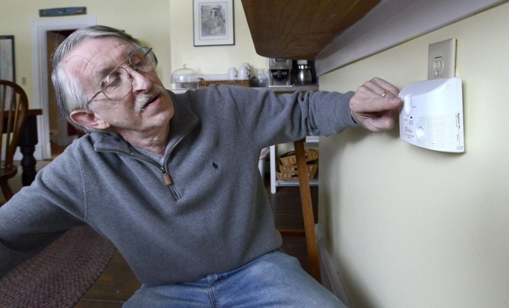 """Owner Tim Rudolph checks a plug-in carbon monoxide detector at the Kendall Tavern Inn, a bed-and-breakfast in Freeport. Rudolph said he and his wife bought the unit several years ago and they keep it in their kitchen. """"You don't even see it,"""" he said."""