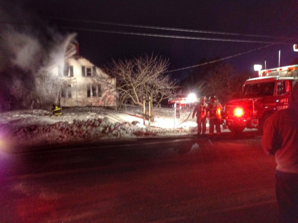 Firefighters from several communities fight a fire at a farmhouse on Route 117 in Hollis on Wednesday.