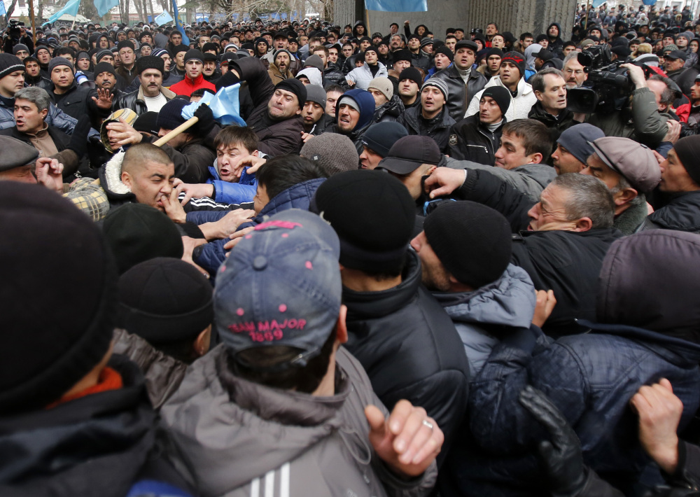 Pro-Russian protesters, right, clash with Crimean Tatars in front of a local government building in Simferopol, Crimea, Ukraine, on Wednesday. More than 10,000 Muslim Tatars rallied in support of the interim government. That group clashed with a smaller pro-Russian rally nearby.