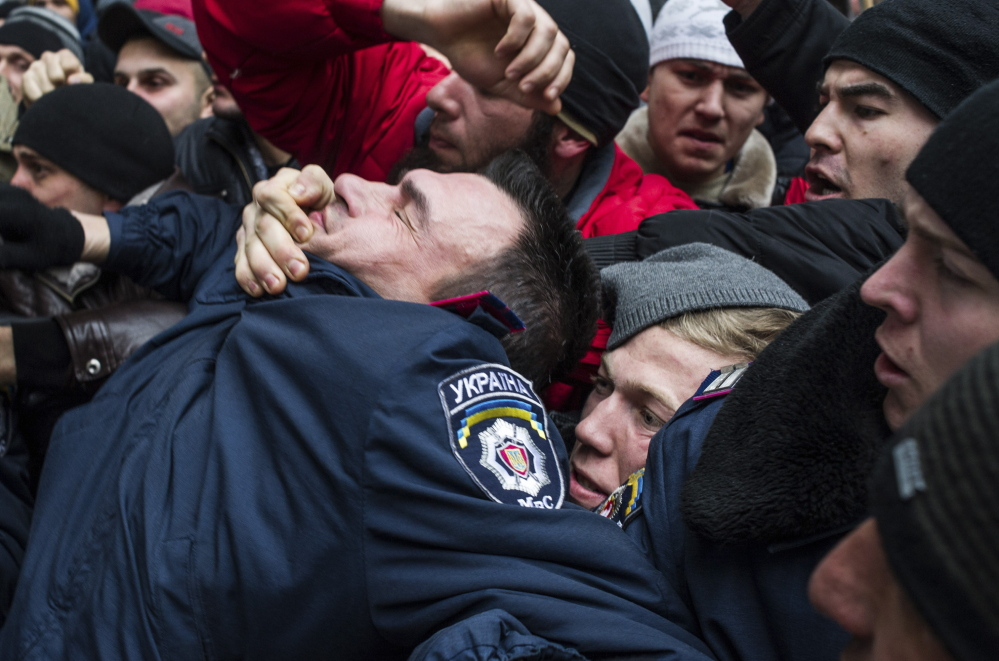 Crimean Tatars grab a police officer in front of a local government building in Simferopol, Crimea on Wednesday.