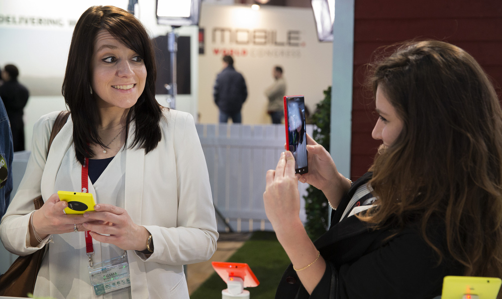 A woman takes a picture of her friend with a Nokia Lumia 1520 phone this week at the Mobile World Congress in Barcelona, Spain. Wireless companies at the show displayed smartphones with much-improved camera software.