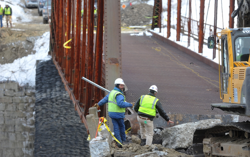 Crews stand by as an excavator jack-hammers the New Sharon bridge on Thursday after the initial controlled explosions failed to bring down the historic structure.