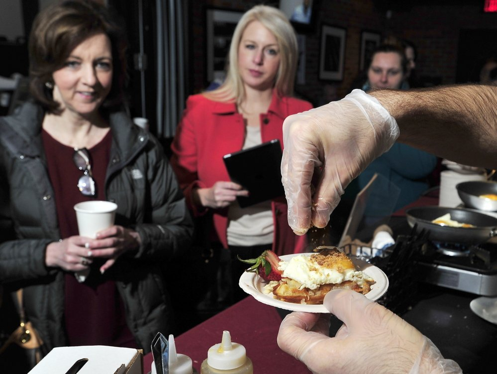 Catherine Dascanio, left, Portland, and Erica Archer of Scarborough await their freshly prepared Pork Belly Waffle with egg sunny-side-up with Maple Bacon Crunch sprinkled by Eve's Chef Tim Labonte, who won this year's Incredible Breakfast Cook-Off.