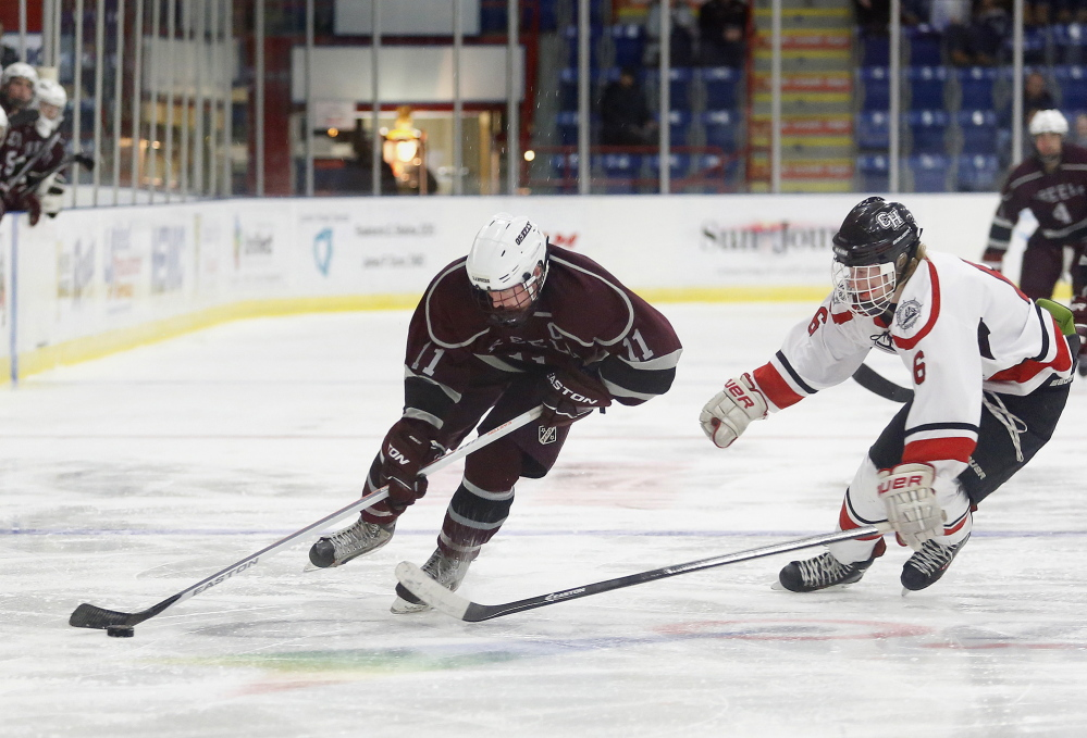Aidan Black of Greely skates past Parker Lawson of Camden Hills, Friday, Feb. 28, 2014, during the Class B West semifinal game at the Colisee in Lewiston.