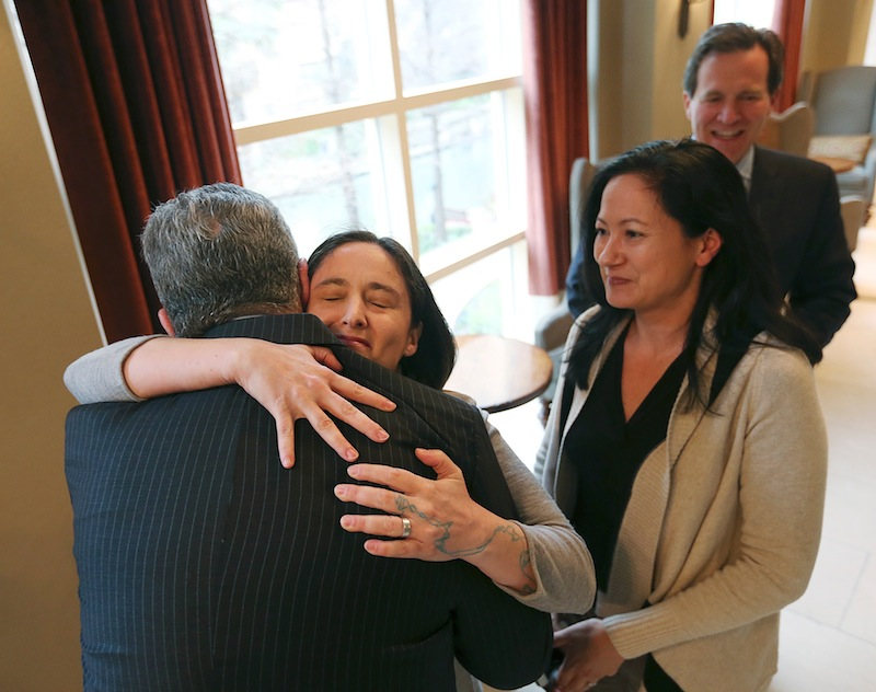 Nicole Dimetman hugs attorney Barry Chasnoff as her partner, Cleopatra De Leon, waits to greet him before a news conference in San Antonio on Wednesday, after U.S. Federal Judge Orlando Garcia declared a same-sex marriage ban in deeply conservative Texas unconstitutional.