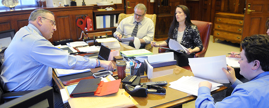 Gov. Paul LePage reaches for a pen while working on his third State of the State address Monday with his Chief of Staff John McGough, right, Press Secretary Adrienne Bennett and Director of Communications Peter Steele in the governor's office in Augusta.