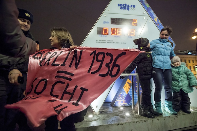 """A gay rights activist holds a banner in front of a large clock showing the number of days left until the start of the Olympic games as police officers approach, left, in St. Petersburg, Russia, Wednesday, Feb. 5, 2014. Russian gay rights activists protested the upcoming Olympic Games in Sochi. Two activists unfurled banners reading """"Berlin 1936 = Sochi 2014,"""" referring to the Olympic Games that were held in the capital of Nazi Germany. One-man pickets are legal in Russia and the two activists holding signs were spaced far enough apart that neither was arrested."""