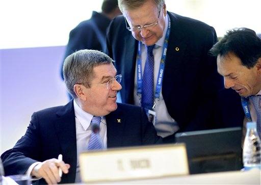 International Olympic Committee President Thomas Bach, left, talks with Director General Christophe De Kepper, right, and executive board member John Coates, prior to opening the IOC's general assembly at the 2014 Winter Olympics, Wednesday, Feb. 5, 2014, in Sochi, Russia. (AP Photo/David Goldman)