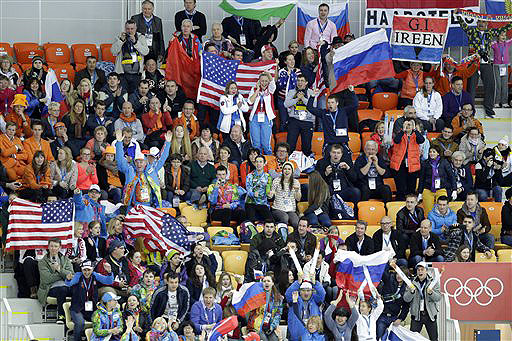 Fans wave their respective national flags and watch the women's 3,000-meter speedskating race at the Adler Arena Skating Center on Sunday during the 2014 Winter Olympics in Sochi, Russia. Many foreigners who have made it to Sochi fall into three camps: experienced world travelers who aren't easily spooked, die-hard Olympic regulars.