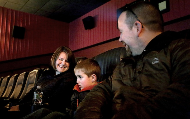 Erin and Aaron Geyer of Parsonsfield and their son, Ethan, 6, watch a sensory friendly showing of