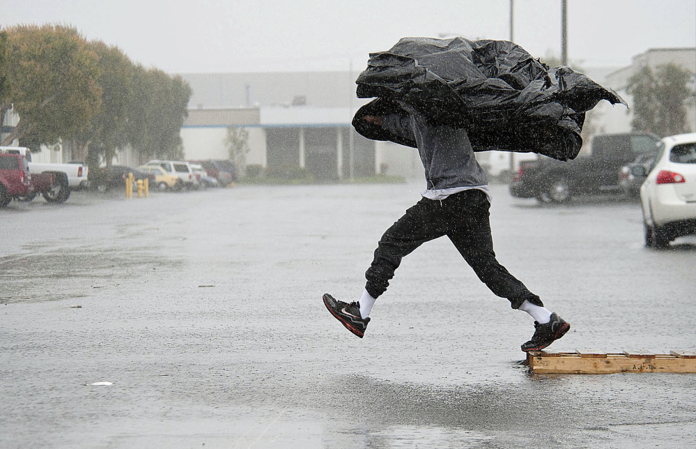 Worker Terry Young of Rialto, Calif., uses a sheet of plastic to protect himself from a downpour Friday as he jumps a flooded parking lot from a wood pallet to get to a food truck during his break in Anaheim, Calif.