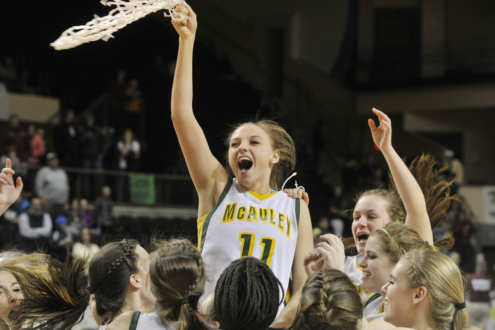 Olivia Smith twirls the net as McAuley players celebrate after beating Oxford Hills 67-41 Saturday afternoon at the Cumberland County Civic Center to win their fourth consecutive Class A girls' basketball state championship.