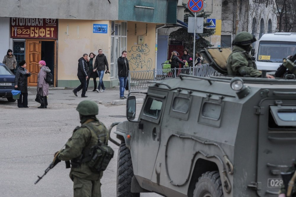 Troops in unmarked uniforms stand guard in Balaklava as people walk in a street, on the outskirts of Sevastopol, Ukraine, on Saturday. An emblem on one of the vehicles and their number plates identify them as belonging to the Russian military.