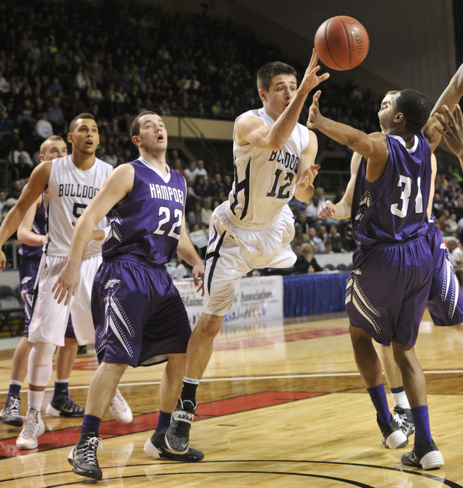 Portland's Justin Zukowski passes off to a teammate after driving between Hampden Academy's Matt Martin, left, and Isaiah Bess during the Class A boys' basketball state championship game Saturday at the Cumberland County Civic Center. Portland won, 54-40.