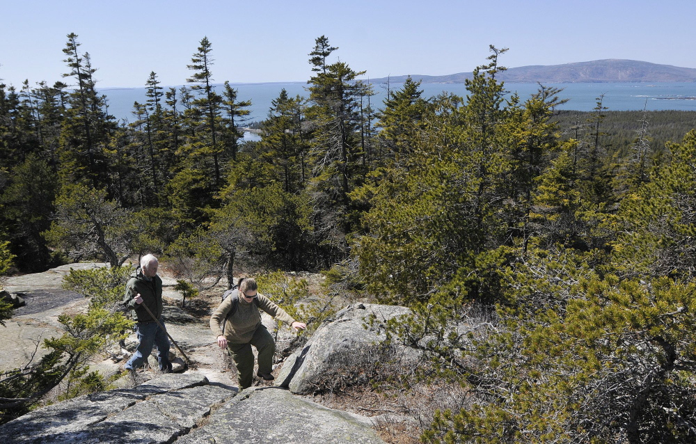 Hikers explore Schoodic Head in Acadia National Park in 2011. In the background are the Atlantic Ocean and Cadillac Mountain. Fewer than 95,000 people visited Acadia in October 2013.