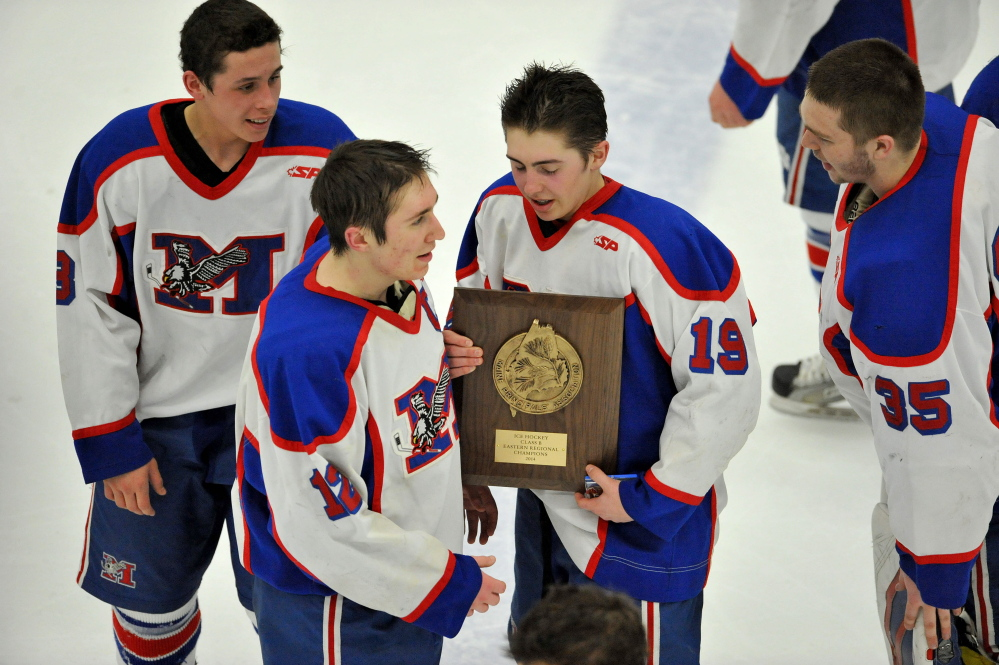 Jared Cunningham, 19, holds the championship plaque afrer Messalonskee earned its third straight Eastern Class B boys' hockey title with a 9-3 win Tuesday over Presque Isle at Alfond Arena in Orono.