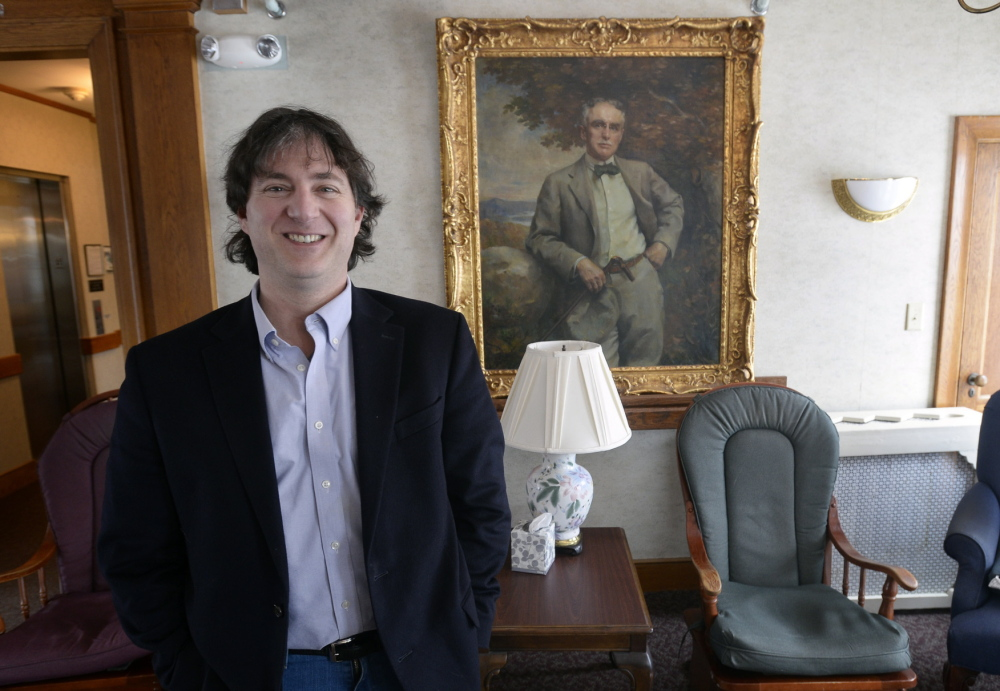 Don Capoldo, executive director of the Plant Home, a nonprofit assisted living center in Bath, poses with a portrait of founder Thomas Plant in the background.
