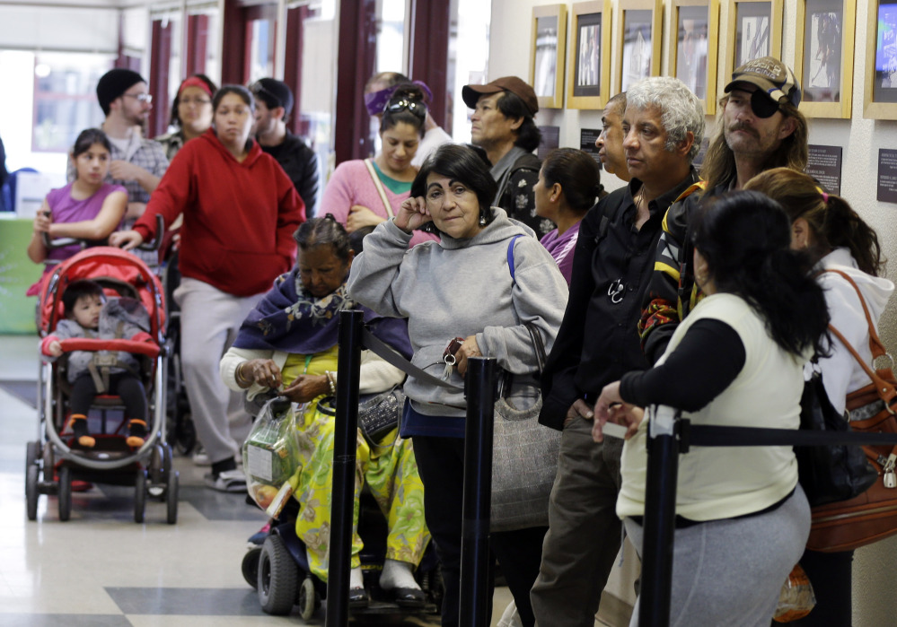 People wait at a food pantry at Sacred Heart Community Center in San Jose, Calif. Silicon Valley is entering its fifth year of growth, with the largest share of high-growth, high-wage jobs. But tens of thousands of area workers don't share in that bounty.