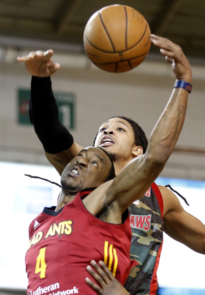 Maine's Sherwood Brown, back, fights for a rebound against Fort Wayne's Chris Porter during Thursday night's game at the Portland Expo, won by the Mad Ants.