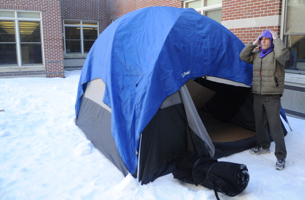 Cony High School English department chairman Tom Wells covers up his head Thursday while preparing a tent at the school to sleep in over night. Four Cony High School teachers were chosen by students to spend the night outside at the school as part of a fundraiser for the Augusta warming center.