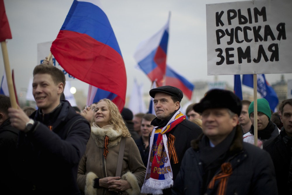"""Pro-Putin demonstrators hold Russian national flags and posters reading """"Crimea is Russia!"""" as they gather in Moscow's Red Square on Friday. Leaders of both houses of parliament said they would support a vote by Crimeans to split with Ukraine and join Russia – signaling for the first time that the Kremlin was prepared to annex the strategic region."""