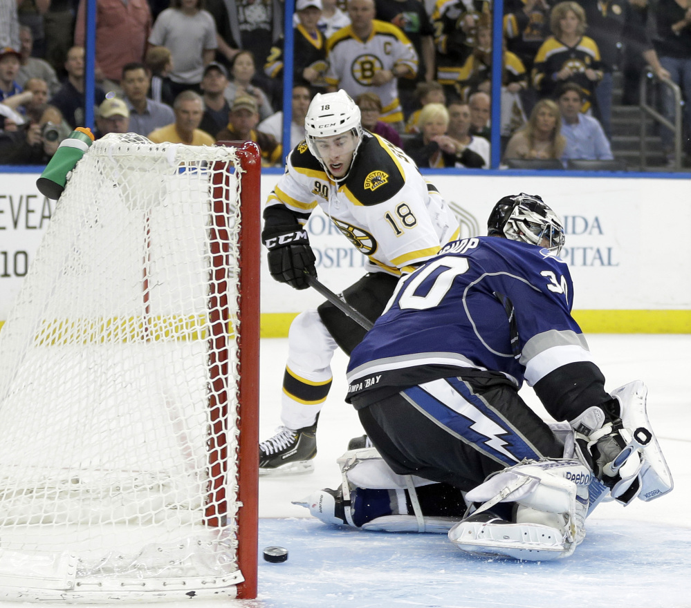 Boston's Reilly Smith slips the puck under Tampa Bay goaltender Ben Bishop for the lone goal in Saturday's shootout that resulted in a 4-3 victory for the Bruins.