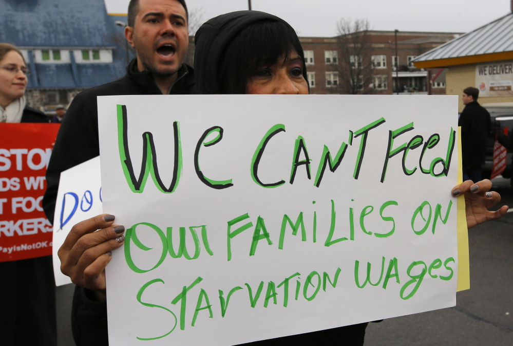 Gladys Jimenez holds a sign during a demonstration in support of higher minimum wages for fast food and other workers outside a Burger King restaurant in Boston in December. Democrats led by President Obama have pushed to raise the federal minimum.