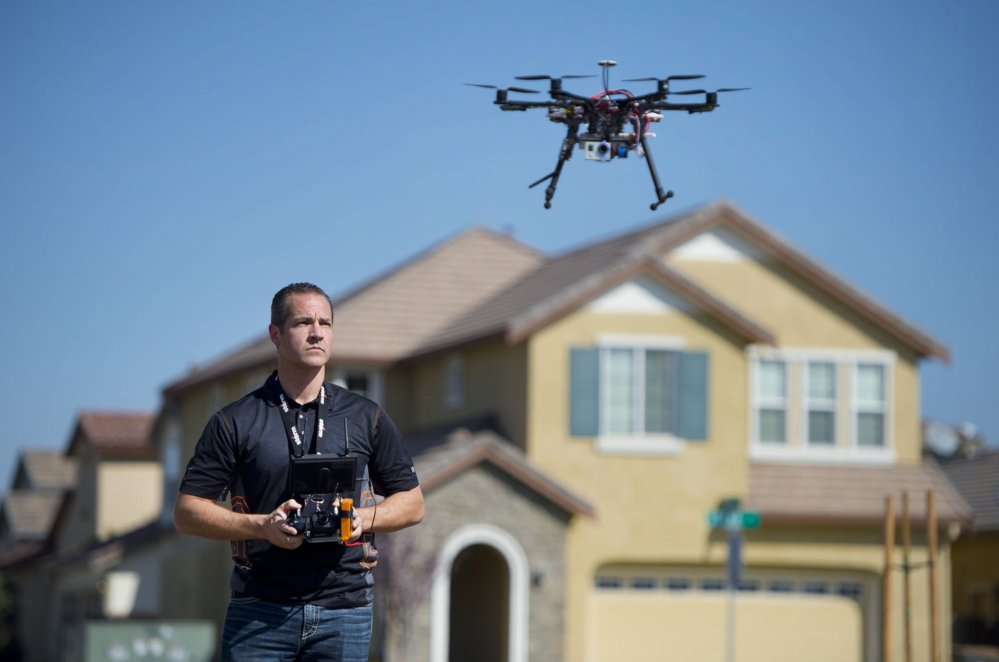 """Christopher Brown of Next New Homes Group uses a multi-rotor drone to take aerial video of a house in Sacramento, Calif. He calls the drones a """"game-changer"""" for marketing homes."""