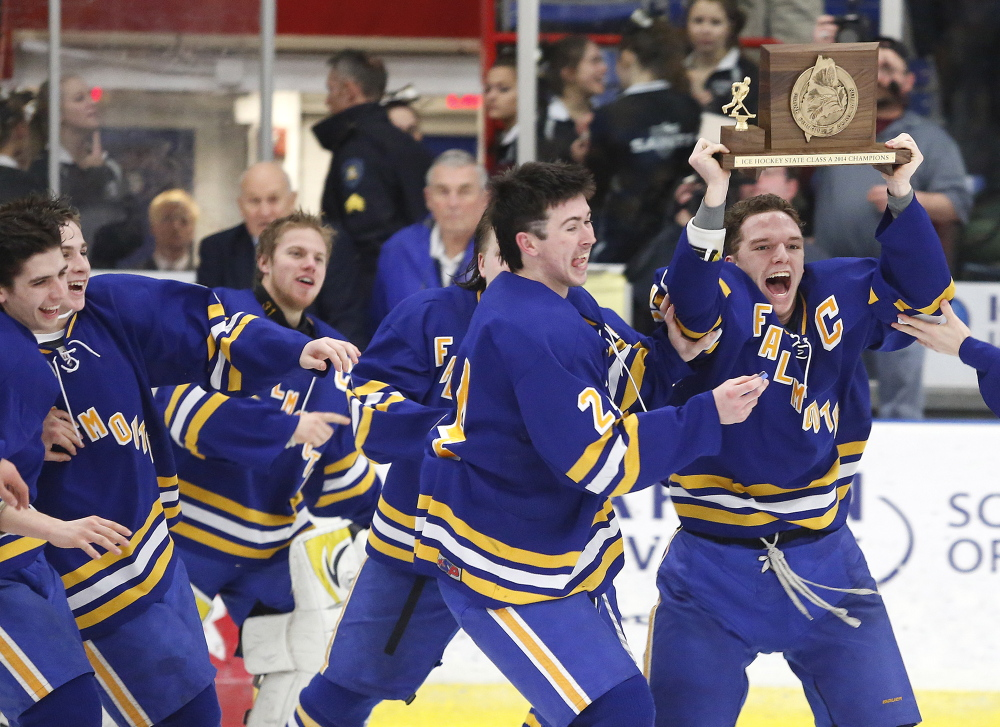 Jake Grade joins Andre Clement (with trophy) and teammates in the celebration Saturday after Falmouth defeating St. Dominic Academy 3-2 in overtime to win the Class A boys' hockey state Championship at the Colisee in Lewiston.