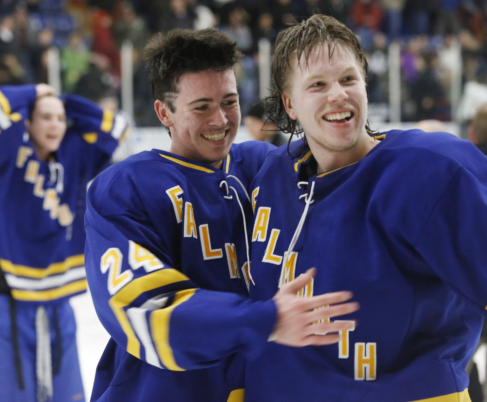Jake Grade, left, and Isac Nordstrom celebrate after Grade scored the overtime goal that put Falmouth atop Class A hockey in the state for the second straight season.