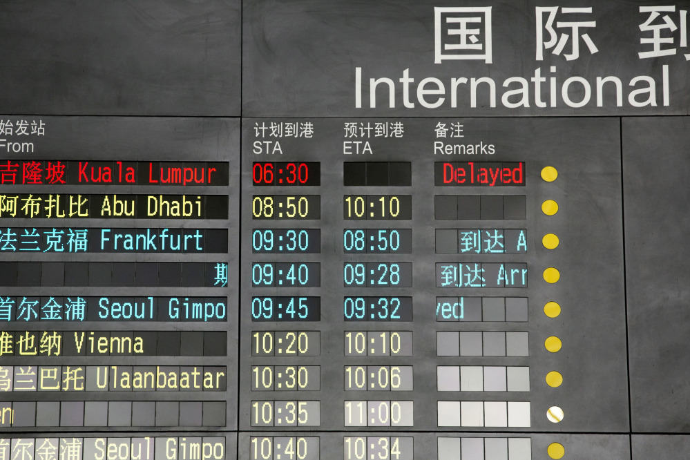 The arrival board at the International Airport in Beijing, China shows a Malaysian airliner is delayed, Saturday.