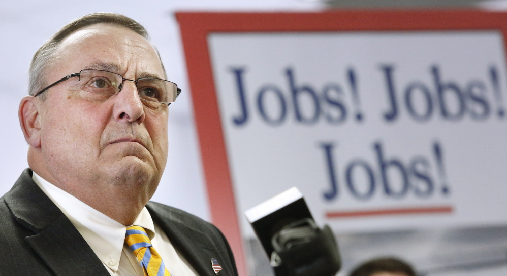 """With a backdrop proclaiming his mission, Gov. Paul LePage holds a news conference Monday to roll out his proposed """"Open for Business Zones"""" inside the Maine Technology Institute at Brunswick Landing."""