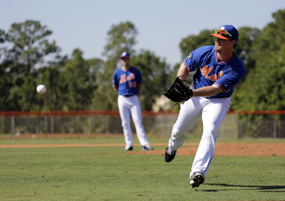 New York Mets pitcher Ryan Reid flips a ball home during a drill at spring training practice Feb. 19 in Port St. Lucie, Fla. He has signed with the Marlins for 2015.