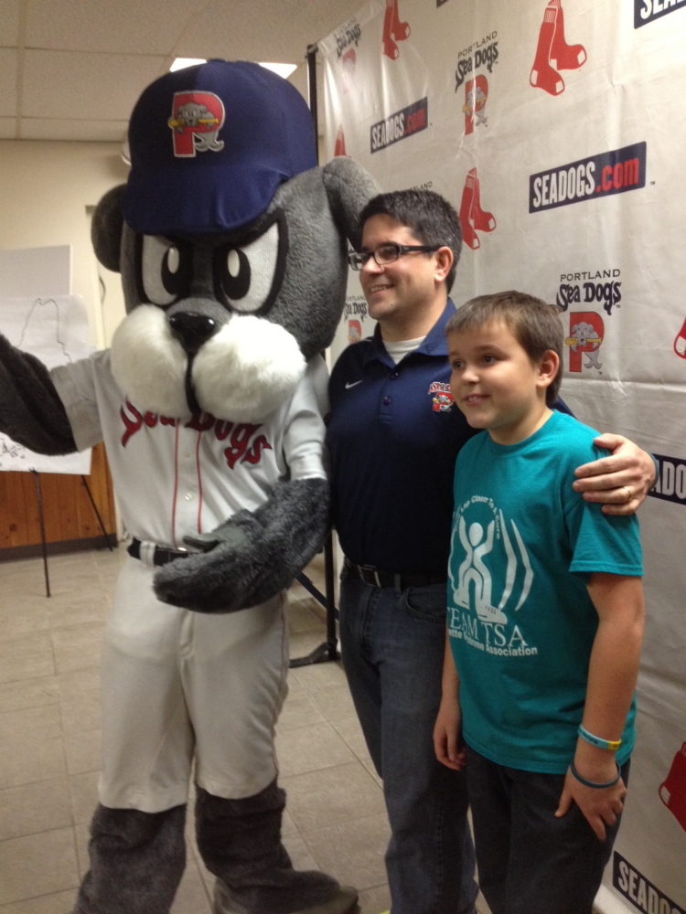 Justin LeBlanc, center, who animated Slugger for the first three years of the franchise's existence in Portland, will walk with the Sea Dogs mascot from Fenway to Hadlock to raise funds for children with Tourette's syndrome. At right is LeBlanc's son Theo, who has Tourette's.