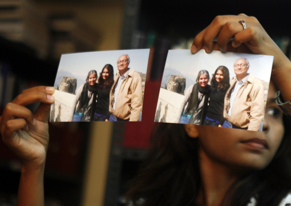 """Photographs showing one of the passengers of the missing Malaysian Airlines aircraft Chandrika Sharma, left, her husband, Narendran, and daughter Meghna, are displayed during a news conference in Chennai, India, Wednesday. Narendran criticized the Indian government for its """"silence"""" and said no government official has contacted the family about the incident, according to a local news agency."""