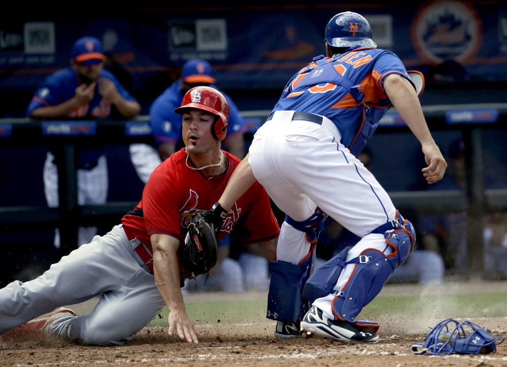 Randal Grichuk is tagged out at home by Mets catcher Taylor Teagarden in the fifth inning of an exhibition spring-training game Wednesday at Port St. Lucie, Fla. The Cardinals won, 6-4.