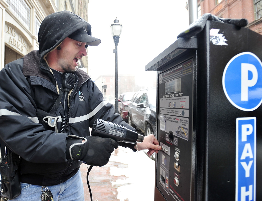 Tom Jarvais, parking meter supervisor for Portland, uses a hand-held heat gun Thursday to thaw out the frozen buttons on one of the new solar-powered pay-to-park stations on Exchange Street. The city invested $465,000 in the machines, which accept debit and credit cards in addition to coins, and are meant to take the place of coin-only meters. Thursday's incident was the second time the units malfunctioned this winter.