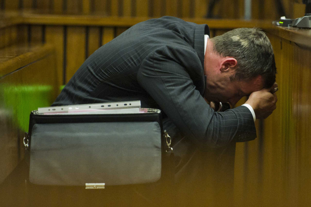 Oscar Pistorius puts his hands to his head as he listens to forensic evidence during his trial in court in Pretoria, South Africa, Thursday. Pistorius is charged with the shooting death of his girlfriend Reeva Steenkamp on Valentines Day in 2013.