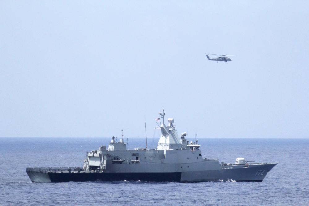 The Royal Malaysian Navy corvette KD Terengganu and a U.S. Navy MH-60R Sea Hawk helicopter conduct a coordinated air and sea search for a missing Malaysian Airlines jet in the Gulf of Thailand.