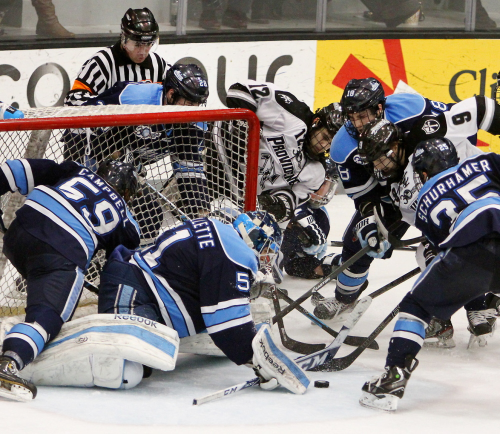 Maine goalie Martin Ouellette keeps the puck out of the net with help from his defense Friday night in Game 1 of the Hockey East quarterfinals at Providence, R.I. The Black Bears lost to Providence 3-1 and must beat the Friars two straight to avoid elimination.